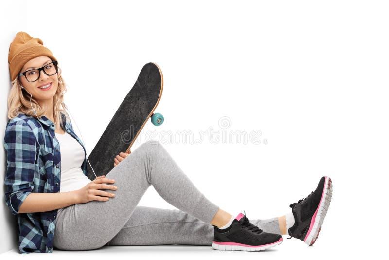 Música que escucha del patinador de sexo femenino en los auriculares imágenes de archivo libres de regalías