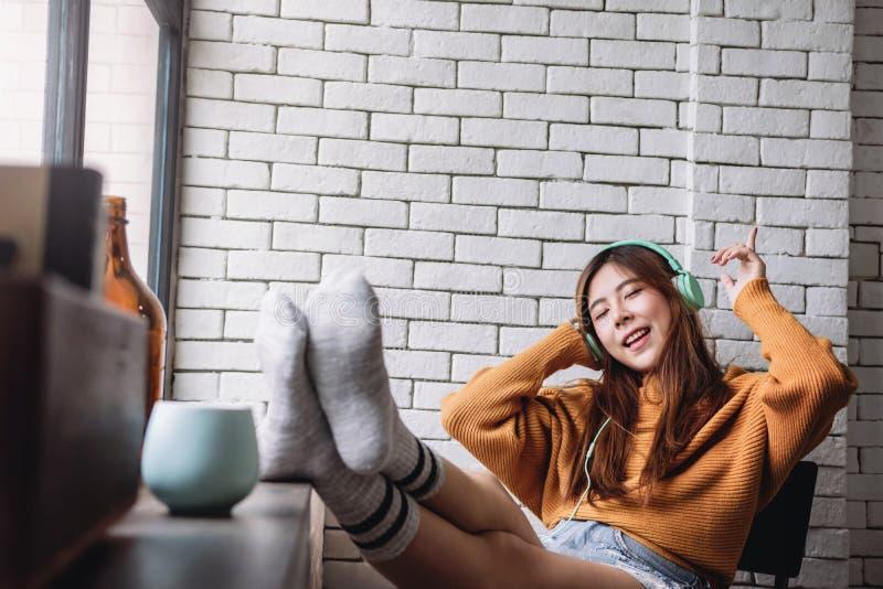 Música que escucha feliz de la mujer joven del auricular en casa acogedora, ojos cerrados y postura alegre fotos de archivo