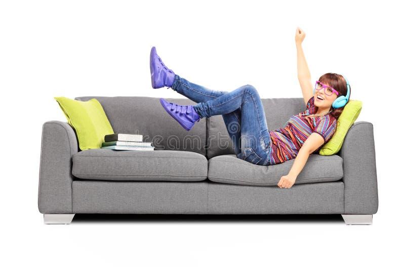 Música que escucha femenina emocionada joven asentada en un sofá fotografía de archivo