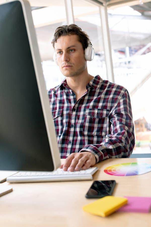 Música que escucha masculina del diseñador gráfico en el auricular mientras que trabaja en el ordenador en el escritorio fotos de archivo libres de regalías
