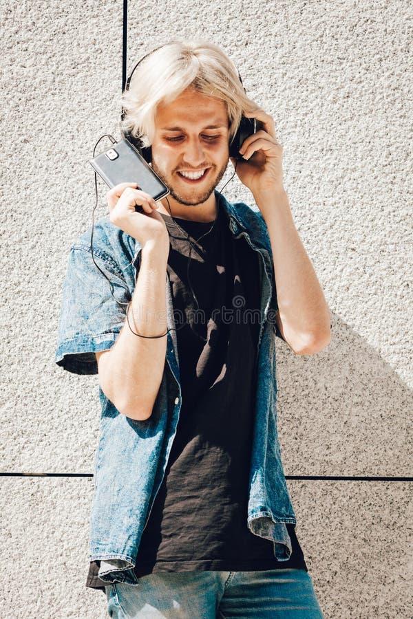 Música que escucha sonriente del hombre del inconformista a través de los auriculares fotografía de archivo libre de regalías