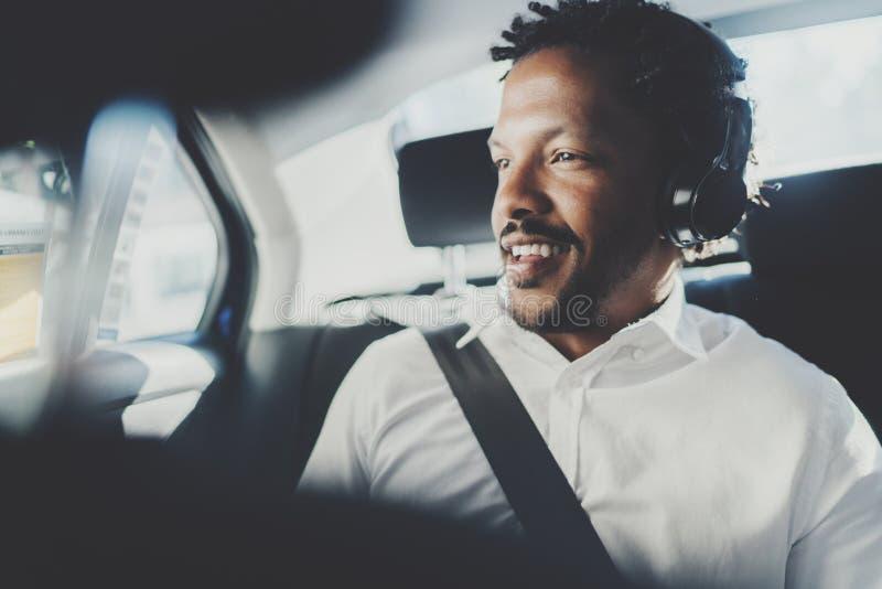 Música que escucha sonriente hermosa del hombre africano en smartphone mientras que se sienta en asiento trasero en coche del tax fotos de archivo