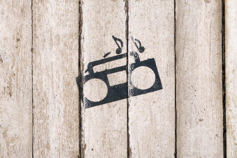 M?sica que juega la muestra y el s?mbolo Grabadora con las notas sobre fondo de madera Servicio de salida Barra, cuidado, club no foto de archivo