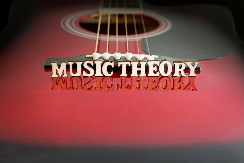 Música rock das palavras com letras de madeira, na superfície refletindo de uma guitarra acústica Perspectiva da ponte das guitar imagens de stock royalty free