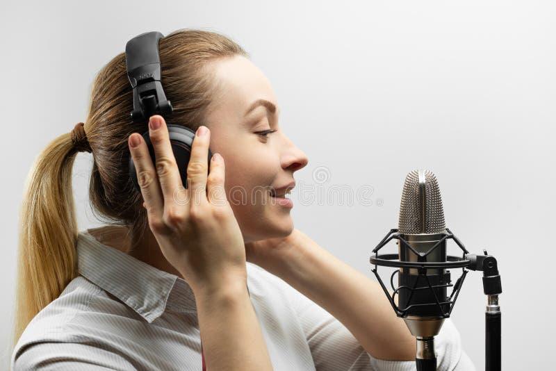 Música, show business, povos e conceito da voz - cantor com fones de ouvido e microfone que canta uma música no estúdio de gravaç fotos de stock