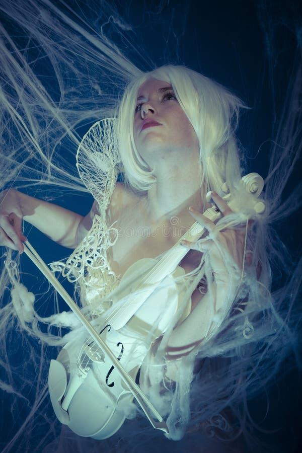 Música, violinista hermoso atrapado en un web de araña fotografía de archivo