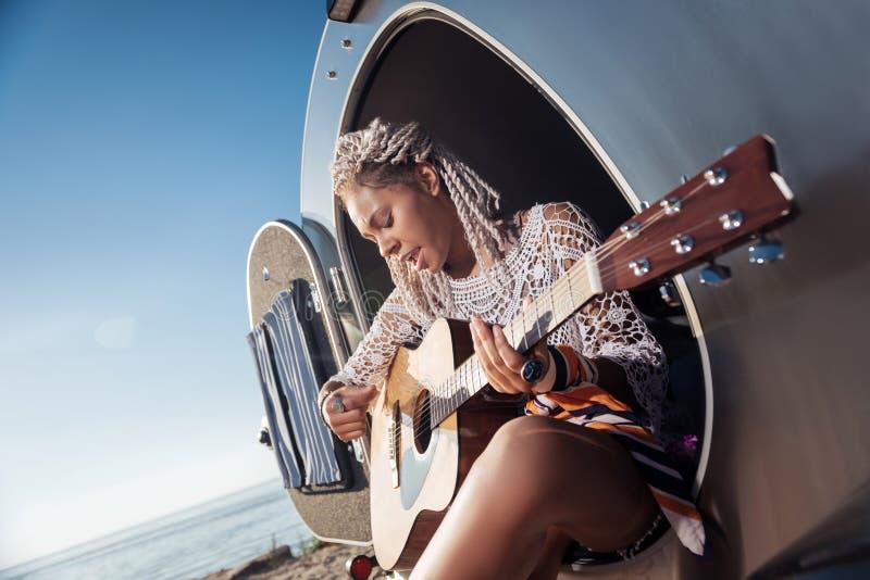 Músico afroamericano que se sienta en la caravana que juega melodía preferida imagen de archivo libre de regalías