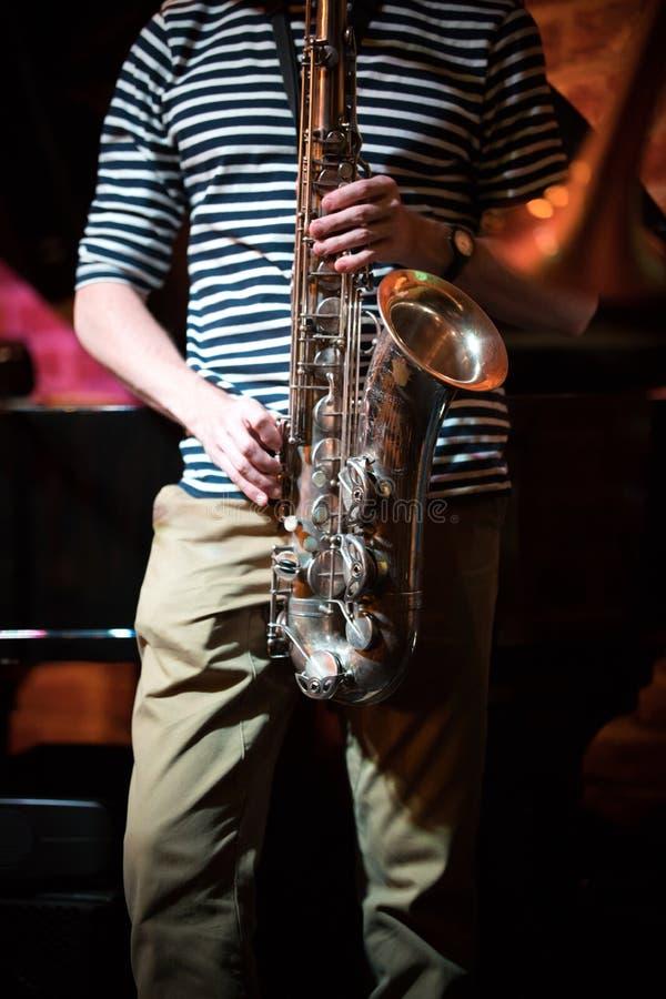 Músico anônimo em um t-shirt listrado que joga o saxofone em um partido em uma barra do jazz imagem de stock