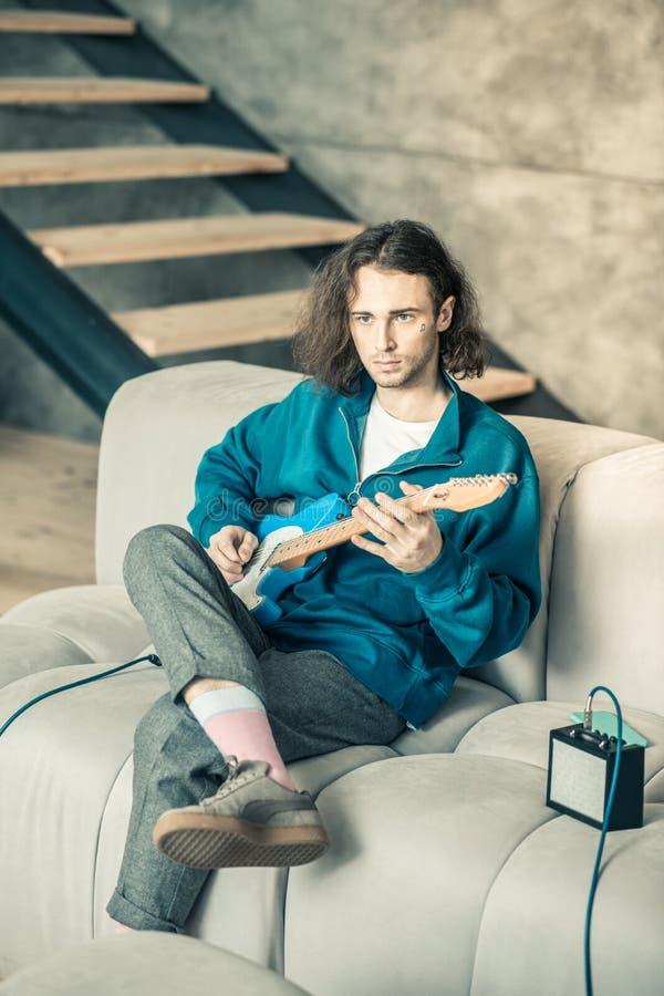 Músico apuesto serio en la sentada superior azul en el sofá gris fotos de archivo libres de regalías