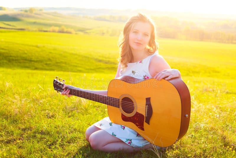 Músico canhoto fêmea novo que joga o instrumento da guitarra na natureza fotos de stock royalty free