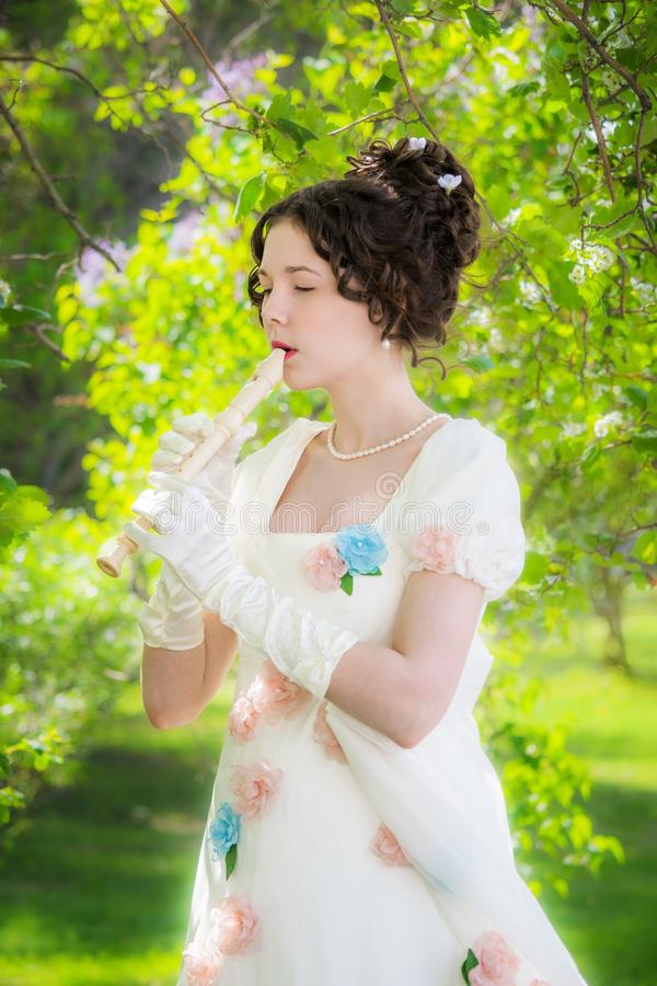 Músico da menina do retrato com uma flauta no jardim imagens de stock