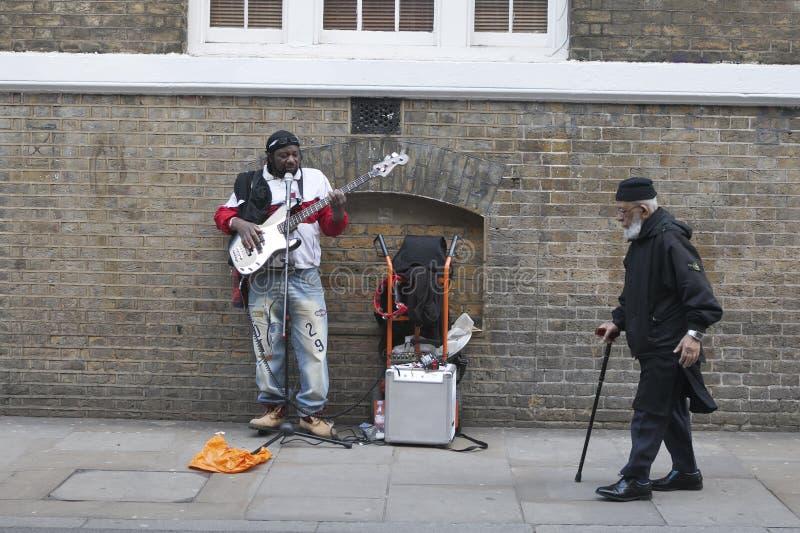 Músico de la calle que toca la guitarra, mientras que un viejo hombre con un bastón camina más allá de él fotografía de archivo libre de regalías