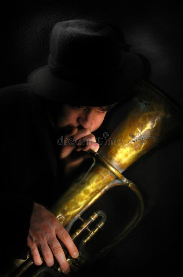 Músico de la calle un fondo oscuro pintado con la luz foto de archivo