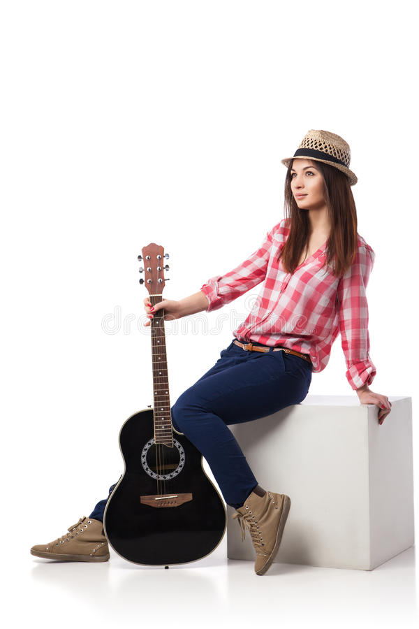 Músico de la mujer joven con la guitarra que se sienta en el cubo imagenes de archivo