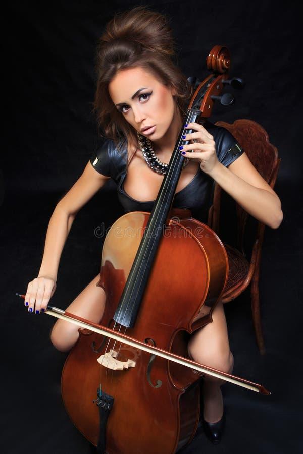 Músico de sexo femenino hermoso que toca un violoncelo fotografía de archivo