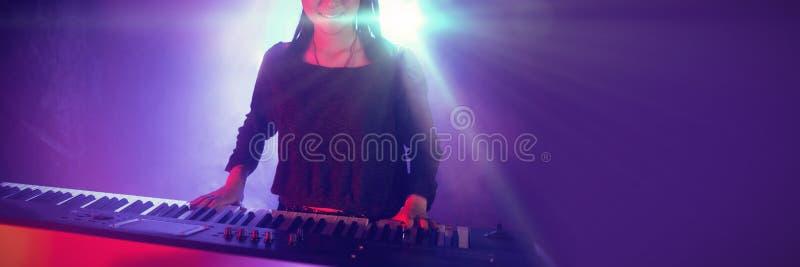 Músico de sexo femenino que juega el piano en club iluminado imagen de archivo libre de regalías