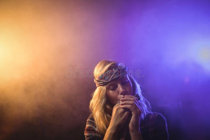 Músico de sexo femenino que toca la armónica en club nocturno fotos de archivo