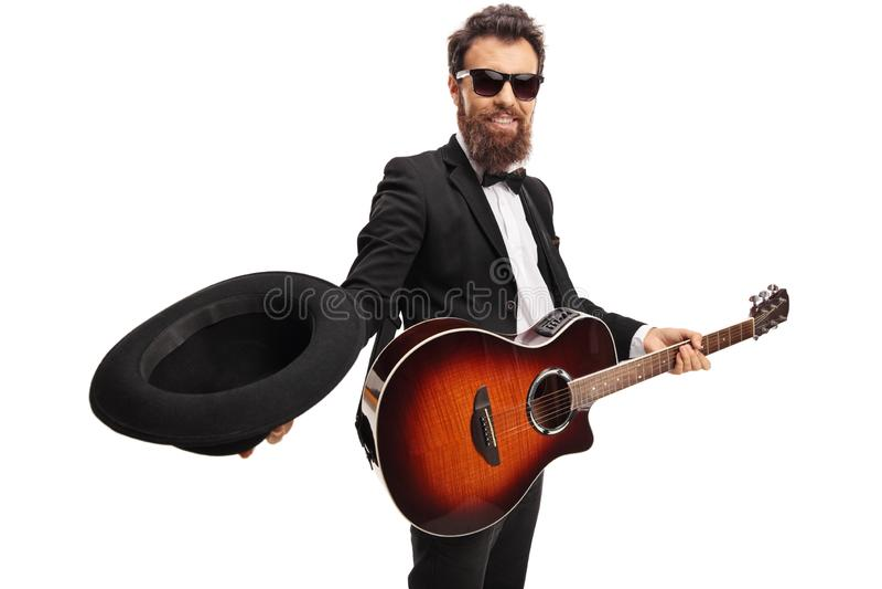 Músico de sexo masculino con una guitarra que sostiene un sombrero para recoger el dinero fotos de archivo libres de regalías