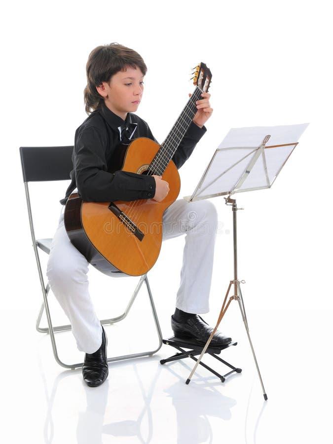 Músico del niño pequeño que toca la guitarra foto de archivo