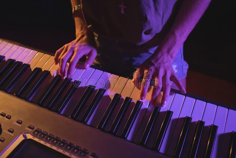 Músico fêmea que joga o piano ao executar no concerto foto de stock