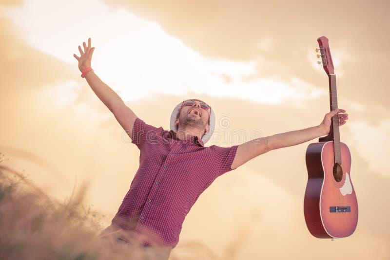 Músico feliz que sostiene la guitarra al aire libre imagen de archivo libre de regalías