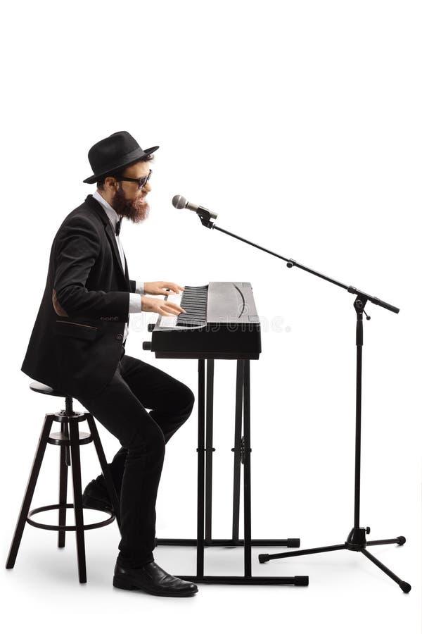 Músico individual tocando el teclado y cantando en el micrófono imagen de archivo libre de regalías