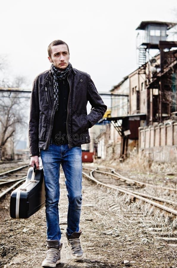 Músico joven con la caja de la guitarra entre ruinas imágenes de archivo libres de regalías