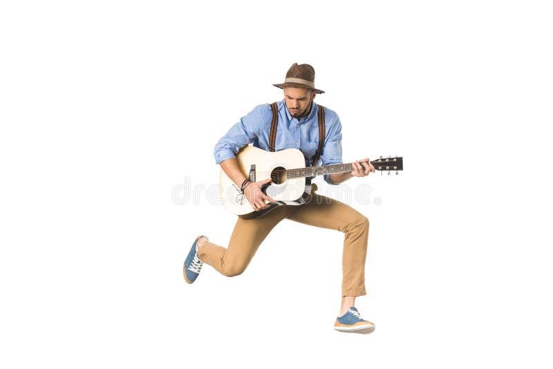 músico joven hermoso en el sombrero que juega la guitarra y el salto fotos de archivo
