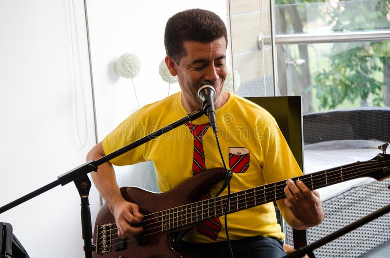 Músico joven hermoso que toca la guitarra fotografía de archivo