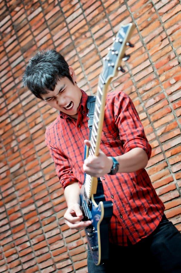 Músico joven hermoso que toca la guitarra fotografía de archivo libre de regalías