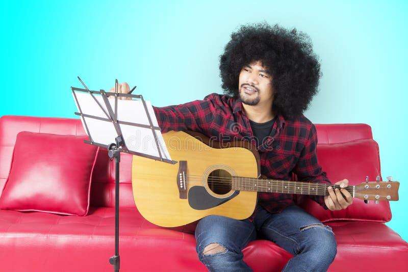 Músico joven que escribe una canción en estudio imagenes de archivo