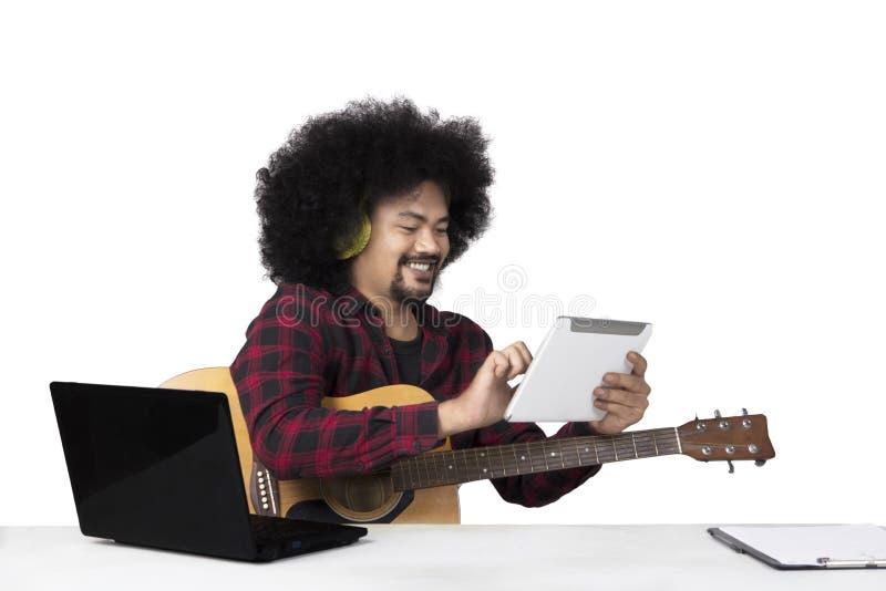 Músico joven que usa la tableta digital imagen de archivo