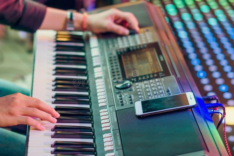 Músico jugar los sintetizadores electrónicos del teclado usando smartphone como instrucciones para jugar en la etapa del conciert fotos de archivo