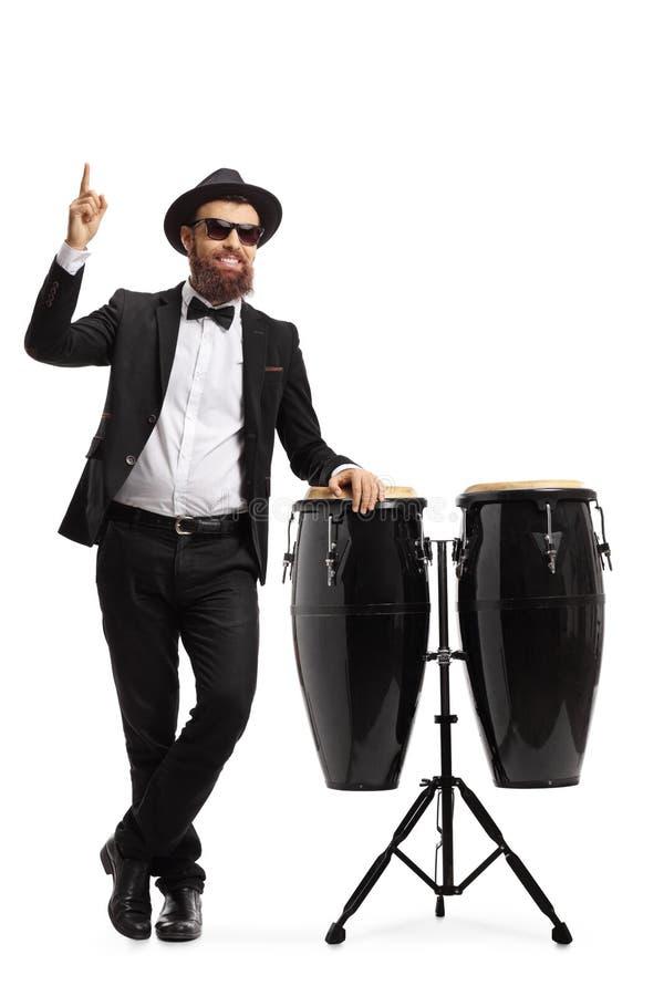 Músico masculino em um terno que levanta ao lado dos cilindros do conga e que aponta acima fotos de stock royalty free