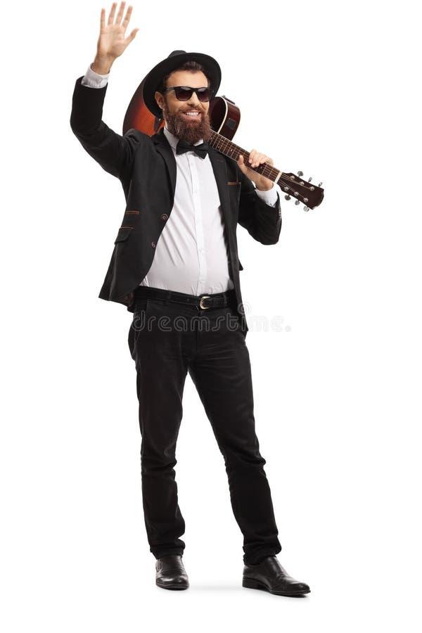 Músico masculino que acena com uma guitarra acústica em seu ombro imagens de stock royalty free