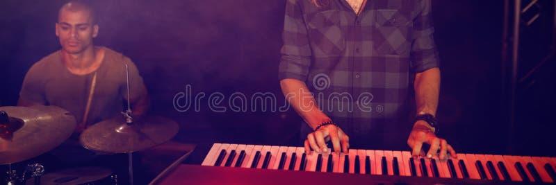 Músico masculino que joga o piano no clube noturno fotografia de stock royalty free