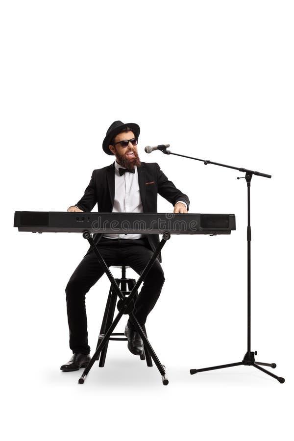 M?sico masculino que joga um piano digital e que canta em um microfone isolado no fundo branco imagens de stock royalty free