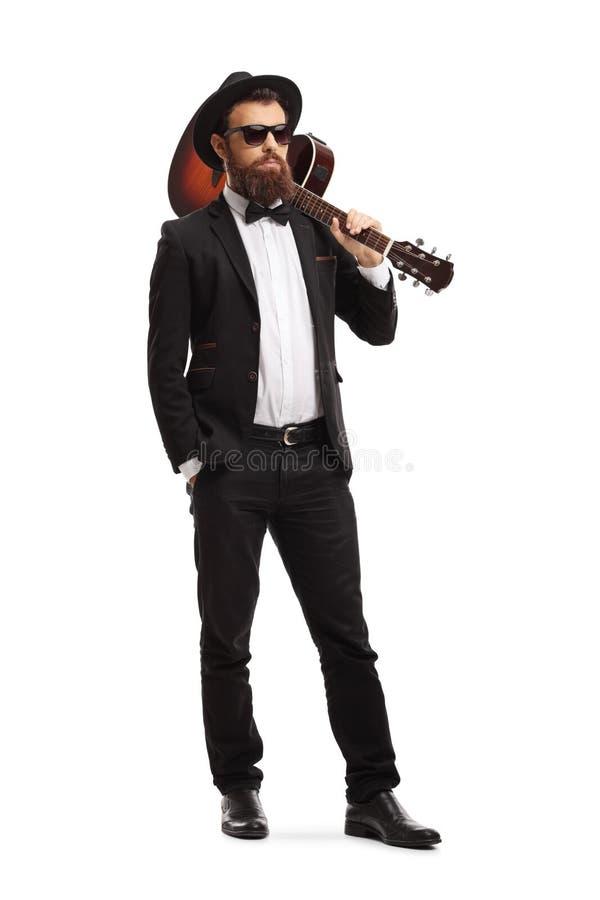 Músico masculino que levanta com uma guitarra acústica em seu ombro imagem de stock royalty free