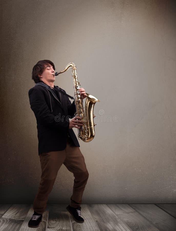 Músico novo que joga no saxofone imagem de stock royalty free