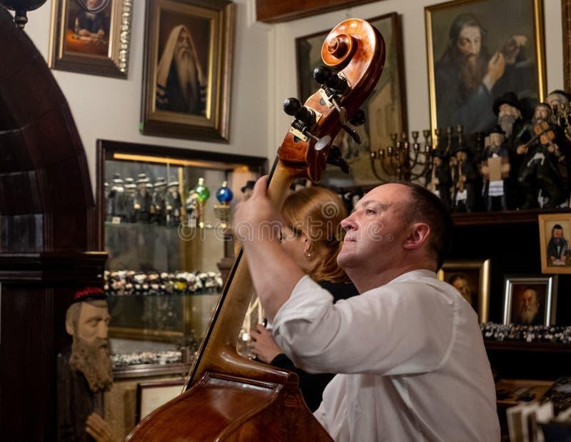 Músico que joga a música do klezmer no restaurante que serve o alimento judaico na rua de Szeroka, Kazimierz, quarto judaico hist foto de stock royalty free