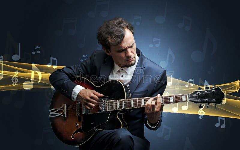 Músico que joga na guitarra com notas ao redor foto de stock royalty free