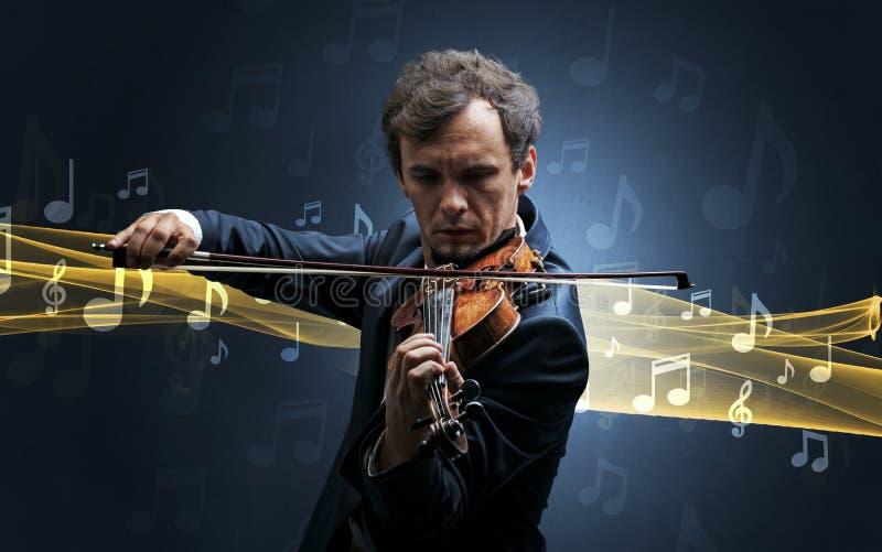 Músico que joga no violino com notas ao redor imagens de stock