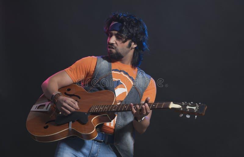 Músico que joga uma guitarra fotografia de stock royalty free