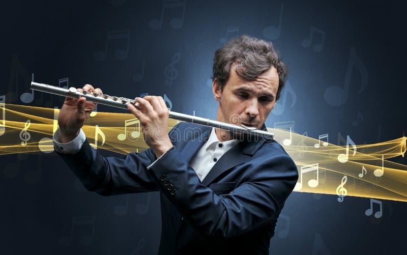 Músico que juega en la flauta con las notas alrededor imagenes de archivo