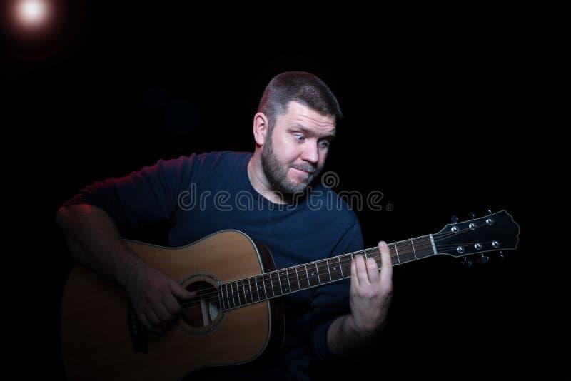 Músico que toca la guitarra acústica imagen de archivo