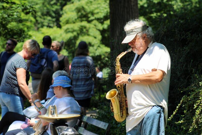 Músico que toca un saxofón en Central Park imágenes de archivo libres de regalías