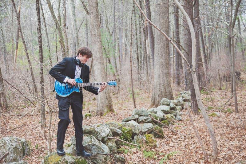 Músico tocando guitarra en el bosque foto de archivo