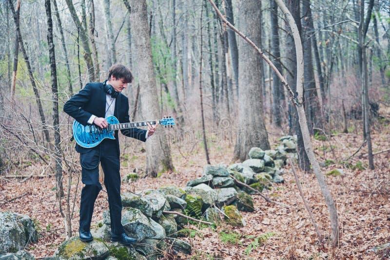 Músico tocando guitarra en el bosque fotografía de archivo libre de regalías