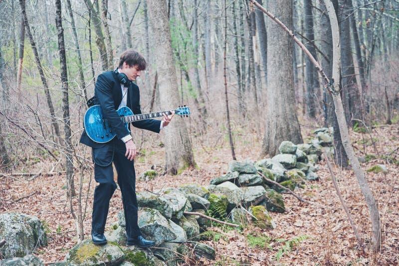 Músico tocando guitarra en el bosque fotos de archivo