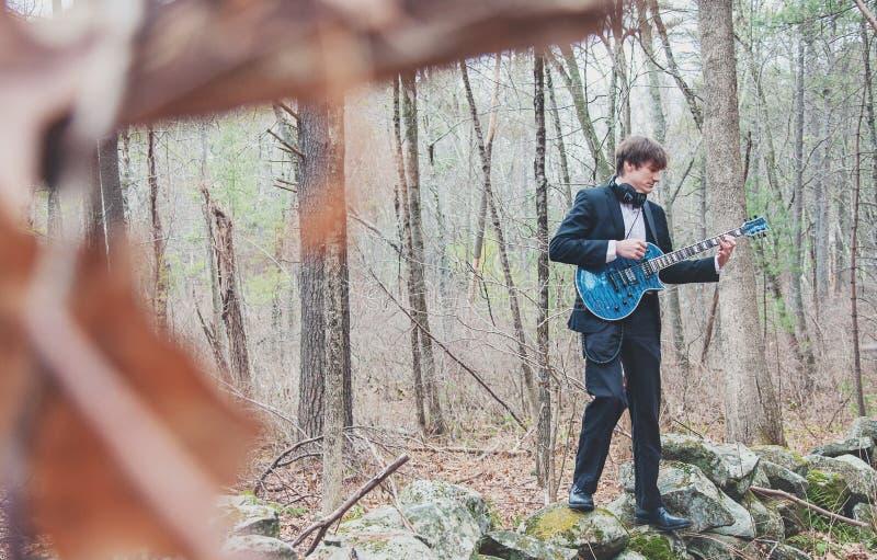 Músico tocando guitarra en el bosque imágenes de archivo libres de regalías